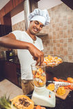Espremedura do cozinheiro chefe frutos com um juicer Foto de Stock Royalty Free