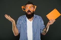 Espressione della meraviglia Nerd del libro che fa un gesto impotente Studente maschio dell'università che indossa i vetri operat immagine stock libera da diritti