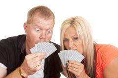 Espressione divertente della donna e dell'uomo dietro le carte da gioco Immagini Stock Libere da Diritti