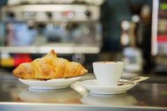 Espresso κινηματογραφήσεων σε πρώτο πλάνο και croissant στον πίνακα στο φραγμό στοκ εικόνες