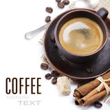 Espresso. Closeup shot of freshly prepared cup of italian espresso with cinnamon, coffe beans, brown sugar and chocolate over white (with sample text Stock Images