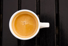 An espresso. In a white cup on a dark wood table stock photo