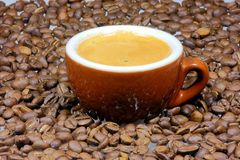 Espresso. A cup of espresso with espresso beans all around Stock Images