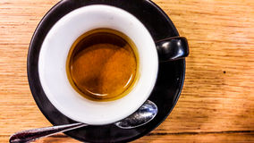 Espresso in black coffee cup on wooden surface. Royalty Free Stock Images