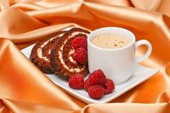 Espresso with cake and raspberries. Espresso cup with cake and raspberries on beige silk background Royalty Free Stock Photos