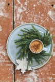 Espresso and christmas cookies on plate with christmas wreath made from pine twigs on wooden table Royalty Free Stock Images