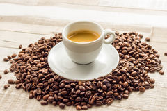 Espresso Coffe mit Bohnen auf Holztischen Lizenzfreie Stockbilder