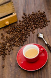Espresso coffe in red cup with arabica beans. And coffee mill Royalty Free Stock Photos