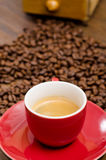 Espresso coffe in a red mug. In front of brown coffee beans Stock Photography