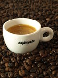 Espresso coffee. Closeup of a cup of espresso coffee with beans in a background stock photography