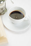 Espresso coffee and book. Espresso coffee with milk in pot and book on white tablecloth Stock Image