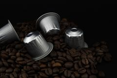 Espresso coffee capsules or coffee pods on coffee beans, black background. Capsules for coffee machine stock image