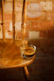 Espresso coffee in clear glass cup on vintage chair with old bri Stock Photos