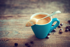 Espresso coffee cup and beans on wooden board. Royalty Free Stock Images