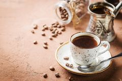 Espresso coffee cup. And coffee beans over brown stone background royalty free stock images