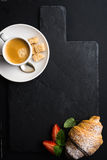 Espresso coffee cup and croissant with fresh strawberries on black  slate stone board over dark background Royalty Free Stock Image