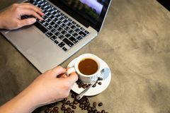 Espresso coffee in a cup of hot coffee and coffee beans,woman hands is working,using a computer,girl fingers typing on the stock photos
