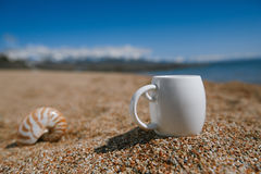 Espresso coffee cup  on the issyk-kul beach sand with mountains Royalty Free Stock Photos