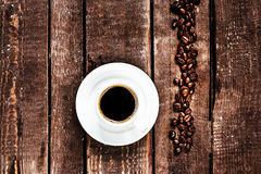 Espresso Coffee cup and roasted  coffee beans on old wooden tabl Royalty Free Stock Image