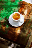 Espresso coffee cup on rustic table with sun Royalty Free Stock Image