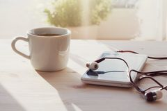 Espresso coffee cup, smartphone and earphones. On wooden table, morning sunlight, listening to music or audiobook, online education at home royalty free stock photos