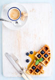 Espresso coffee cup, soft belgian waffles with fresh blueberries and marple syrup on white painted wooden board over Stock Photos