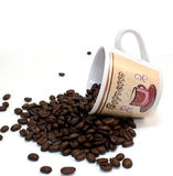Espresso coffee cup spilling coffee beans Royalty Free Stock Image