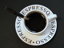 Espresso coffee in cup with spoon. Espresso with spoon handle sticking out of cup royalty free stock photos