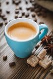 Espresso coffee cup, sugar cubes, coffee beans and spices on wooden desk. Stock Photos