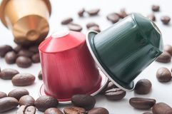 Espresso coffee doses with coffee beans. Closeup of colorful espresso coffee doses with coffee beans on white table background royalty free stock photo
