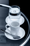 Espresso coffee empty cup and glass of water on bedside table closeup Stock Image