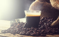 Espresso coffee in glass cup with coffee beans. Royalty Free Stock Images
