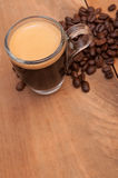 Espresso Coffee. Glass Cup of Espresso Coffee on Wooden Table With Coffee Beans - Shallow Depth of Field stock images