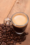 Espresso Coffee. Glass Cup of Espresso Coffee on Wooden Table With Coffee Beans - Shallow Depth of Field royalty free stock photo