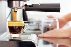 Espresso coffee machine in kitchen. Coffee pouring into cup Stock Photography