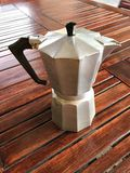 Espresso coffee maker. On wooden table with small glass cup Stock Photo
