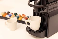 Espresso coffee maker machine with capsules behind it. Close up view with details, blur background. Royalty Free Stock Images