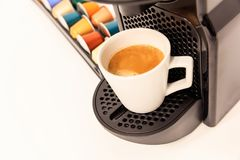 Espresso coffee maker machine in black color, ready coffee, capsules near it. Close up view, detail. Stock Photography