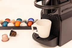 Espresso coffee maker machine with capsules next to it. Close up view with details, blur background. Stock Images
