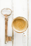 Espresso coffee and old key on white wooden table Stock Image
