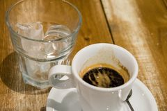 Espresso coffee and glass of ice cubes stock photography