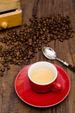 Espresso coffee in a red mug. Surrounded with beans Royalty Free Stock Image