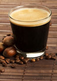 Espresso coffee in a short glass with hazelnuts Stock Images