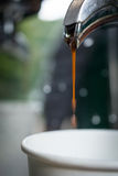 Espresso coffee stream flowing from the inside of coffee machine Royalty Free Stock Photos