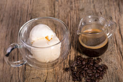 Espresso coffee and Vanilla ice cream in double walled glass italian dessert, with coffee beans on the rustic wooden tab Stock Image