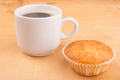Espresso coffee in a white china cup over wood. Espresso coffee in a white china cup and cupcake over wood surface stock photos