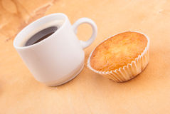 Espresso coffee in a white china cup over wood. Espresso coffee in a white china cup and cupcake over wood surface stock image