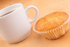Espresso coffee in a white china cup over wood. Espresso coffee in a white china cup and cupcake over wood surface stock photography
