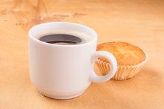 Espresso coffee in a white china cup over wood. Espresso coffee in a white china cup and cupcake over wood surface stock photo