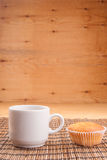Espresso coffee in a white china cup over wood. Espresso coffee in a white china cup and cupcake over wooden mat stock image